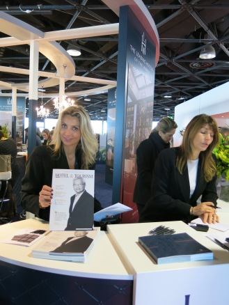 Leading Hotels of the World welcome desk hostess at ILTM Cannes with Hotel&Tourism SMARTreport featuring Ted Teng President & CEO LHW.jpg